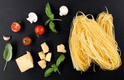Pasta homemade raw and ingredients for pasta. Parmesan cheese, tomatoes, mushrooms, basil Royalty Free Stock Photos