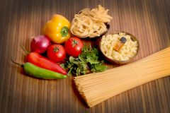 Pasta and ingredients. Beautiful shot of wheat pasta with different types of vegetables on wooden background Royalty Free Stock Photo