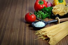 Pasta and ingredients. Beautiful shot of wheat pasta with different types of vegetables on wooden background Stock Photo