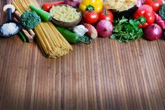 Pasta and ingredients. Beautiful shot of wheat pasta with different types of vegetables on wooden background Stock Photos
