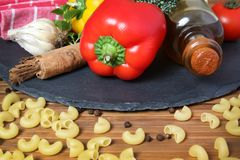 Pasta and ingredients. Beautiful shot of wheat pasta with vegetables and oil Stock Photos