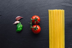 Pasta ingredients on black slate background. Viewed from the top Royalty Free Stock Photography
