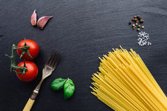 Pasta ingredients on black slate background. Viewed from the top stock photo