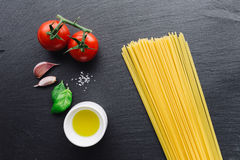 Pasta ingredients on black slate background. Viewed from the top stock images