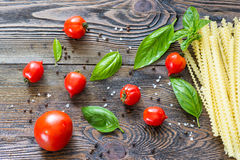 Pasta ingredients. Cherry tomatoes, spaghetti pasta, basil Royalty Free Stock Photography