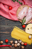Pasta ingredients. Cherry-tomatoes, spaghetti pasta, chicken fillet and mushrooms on the wooden table. Royalty Free Stock Images