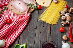 Pasta ingredients. Cherry-tomatoes, spaghetti pasta, chicken fillet and mushrooms on the wooden table Stock Photography