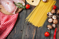 Pasta ingredients. Cherry-tomatoes, spaghetti pasta, chicken fillet and mushrooms on the wooden table. Royalty Free Stock Image