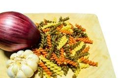 Pasta ingredients. Colourful fusilli, garlic and purple onion on board Stock Photo