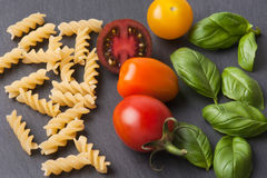 Pasta ingredients concept on black slate background viewed from the top. Tomatoes , pasta and basil. italian food Stock Images