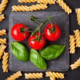Pasta ingredients concept on black slate background viewed from the top. Tomatoes , pasta and basil. italian food Royalty Free Stock Photos