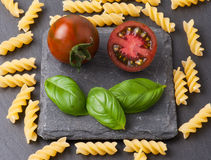 Pasta ingredients concept on black slate background viewed from the top. Tomatoes , pasta and basil. italian food Royalty Free Stock Images