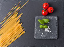 Pasta ingredients concept on black slate background viewed from the top. Tomatoes , pasta and basil. italian food Royalty Free Stock Photo