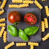Pasta ingredients concept on black slate background viewed from the top. Tomatoes , pasta and basil. italian food Stock Photo