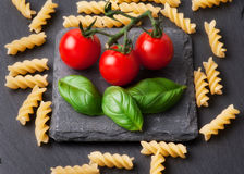 Pasta ingredients concept on black slate background viewed from the top. Tomatoes , pasta and basil. italian food Stock Photography