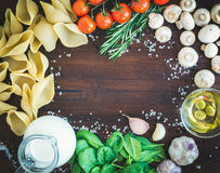 Pasta ingredients: conchiglioni,mushrooms, a jug of cream, olive Stock Photos
