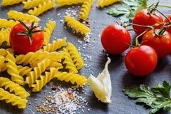 Pasta ingredients (fusilli). On black slate background Stock Image