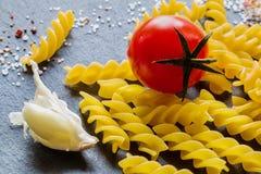 Pasta ingredients (fusilli). On black slate background Stock Photo