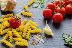 Pasta ingredients (fusilli) on black slate background. Fresh tomatoes, garlic, parsley, salt and pepper Stock Photography