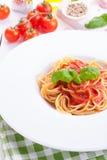 Pasta ingredients - tomatoes, olive oil, garlic, italian herbs, fresh basil, salt and spaghetti on a black stone background Stock Photo