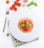 Pasta ingredients - tomatoes, olive oil, garlic, italian herbs, fresh basil, salt and spaghetti on a black stone background Stock Photos
