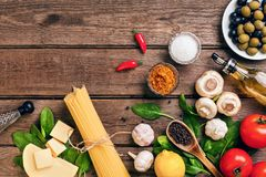Pasta ingredients - tomatoes, olive oil, garlic, italian herbs, fresh basil, salt and spaghetti on a wooden background. With copy space, horizontal, top view royalty free stock photo