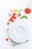 Pasta ingredients - tomatoes, olive oil, garlic, italian herbs, fresh basil and spaghetti and empty plate Royalty Free Stock Photography