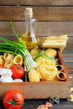 Pasta and ingredients on wooden background Royalty Free Stock Image