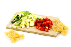 Pasta ingredients on wooden cutting board. Isolated on a white background Royalty Free Stock Photography