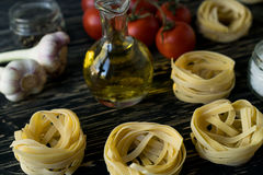 Pasta ingridients and spice on wooden surface. Pasta ingridients and spice on wooden background Royalty Free Stock Images