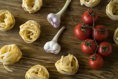 Pasta ingridients and spice on wooden surface. Pasta ingridients and spice on wooden background Stock Image