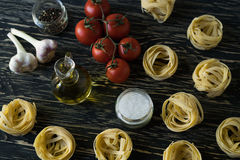 Pasta ingridients and spice on wooden surface. Pasta ingridients and spice on wooden background Royalty Free Stock Photos