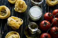Pasta ingridients and spice on wooden surface. Royalty Free Stock Photography