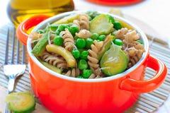 Pasta intera con le verdure verdi in pentola ceramica fotografia stock