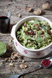 Pasta italian handmade tagliatelle with pesto basil green sauce with pink peppercorn, walnuts on bowl rustic table Stock Photo