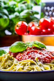 Pasta. Italian and Mediterranean cuisine. Pasta Fettuccine with tomato sauce basil leaves garlic and parmesan cheese. An old home. Kitchen with old kitchen Stock Photography
