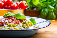 Pasta. Italian and Mediterranean cuisine. Pasta Fettuccine with tomato sauce basil leaves garlic and parmesan cheese. An old home. Kitchen with old kitchen Stock Images