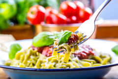 Pasta. Italian and Mediterranean cuisine. Pasta Fettuccine with tomato sauce basil leaves garlic and parmesan cheese. An old home Stock Photography