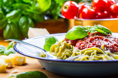Pasta. Italian and Mediterranean cuisine. Pasta Fettuccine with tomato sauce basil leaves garlic and parmesan cheese. An old home. Kitchen with old kitchen Royalty Free Stock Photo