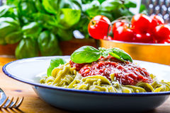 Pasta. Italian and Mediterranean cuisine. Pasta Fettuccine with tomato sauce basil leaves garlic and parmesan cheese. An old home. Kitchen with old kitchen Stock Image