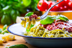 Pasta. Italian and Mediterranean cuisine. Pasta Fettuccine with tomato sauce basil leaves garlic and parmesan cheese. An old home. Kitchen with old kitchen Royalty Free Stock Images