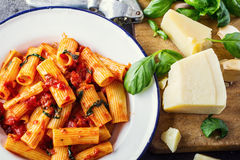 Pasta. Italian and Mediterrannean cuisine. Pasta Rigatoni with tomato sauce basil leaves garlic and parmesan cheese. Stock Image