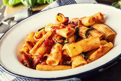 Pasta. Italian and Mediterrannean cuisine. Pasta Rigatoni with tomato sauce basil leaves garlic and parmesan cheese. Stock Photo