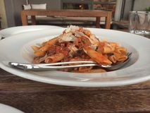 Pasta at Italian restaurant in Bruce Canberra. Pasta with Penne, pancetta, pork sausage, chili, mushroom, garlic shallots, napolitana sauce stock photography