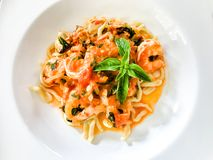 Pasta Italian served with shrimps and basil leaves stock photography