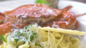 Pasta italiana con il granchio rosso, l'erba fresca ed il formaggio sulla fine bianca del piatto su Pasta tradizionale con frutti stock footage