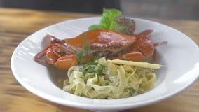 Pasta italiana dei frutti di mare con il granchio rosso e condimento fresco dell'erba in piatto bianco sulla tavola di legno Past video d archivio