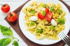 Pasta italiana del farfalle con i pomodori, il basilico e la mozzarella Fotografia Stock