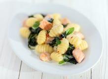 Pasta italiana di gnocchi con il salmone ed il basilico Fotografia Stock