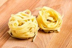 Pasta italiana di tagliatelle sulla tavola di legno Immagine Stock